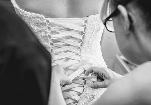 bride having dress fitted
