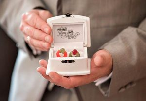 groom holding wedding rings in a box