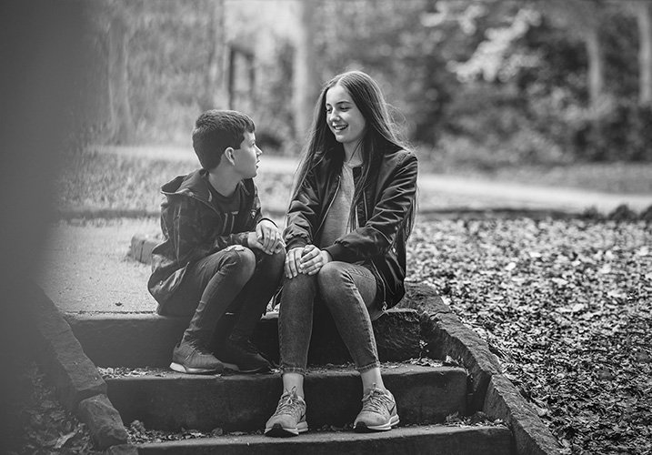 brother and sister sat down chatting - Siblings Photography
