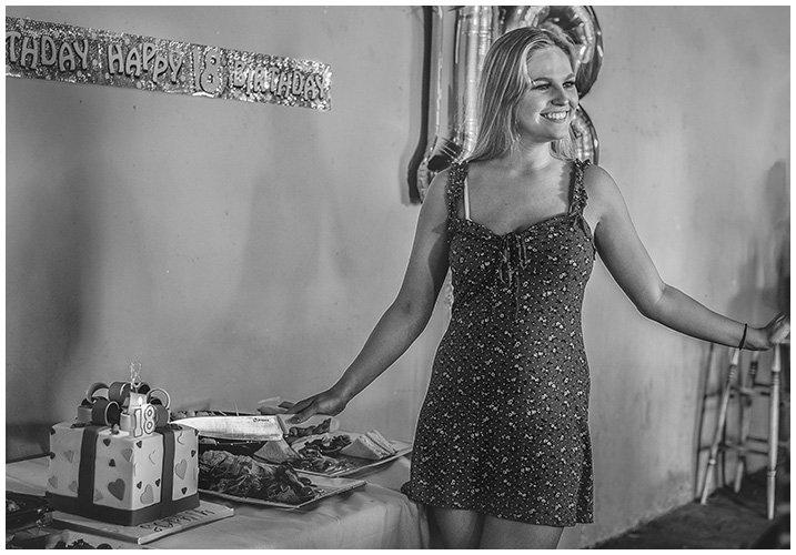 girl 18th birthday cutting cake