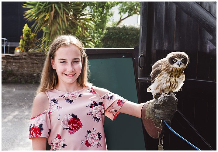young girl holding an owl at a party - Home