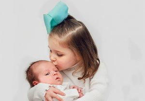 sister kissing her newborn brother 300x209 - Home