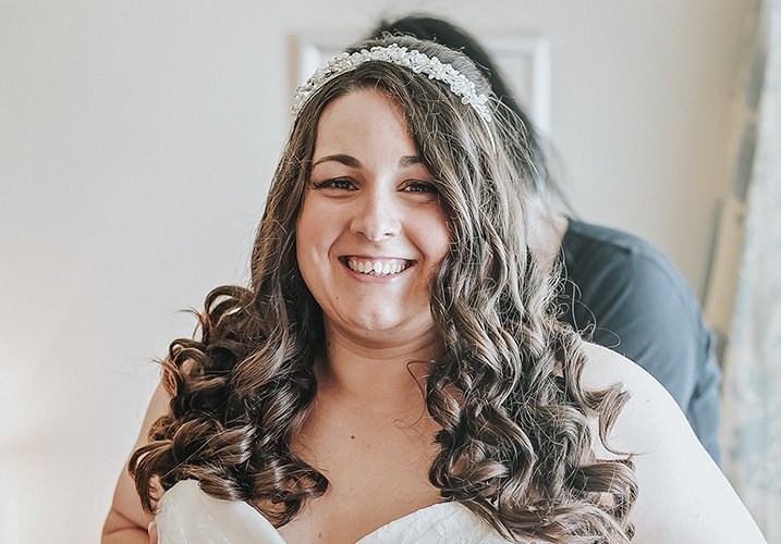 Bride getting fitted into her wedding dress