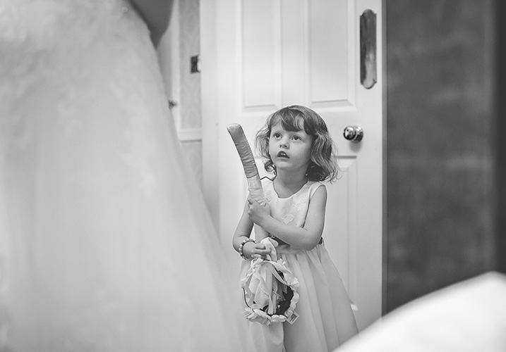 Daughter watching her mum put on her wedding dress - Wedding Photography