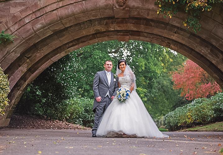 bride and groom under a bridge