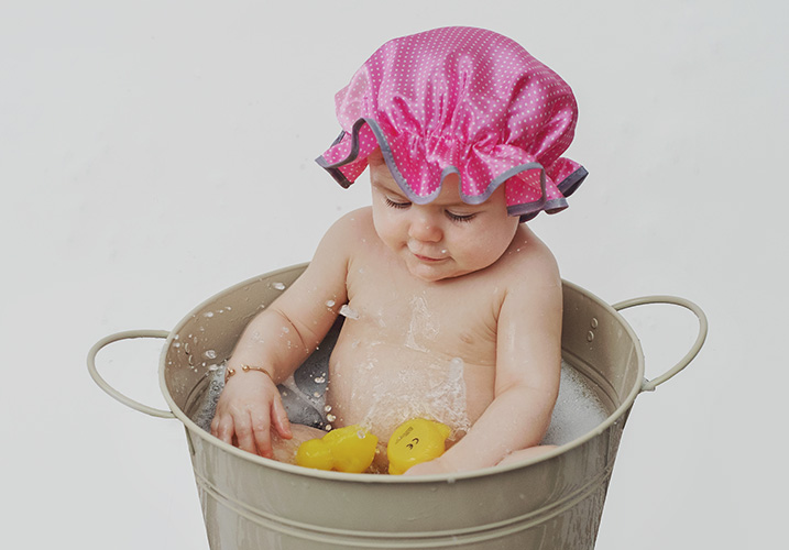 little girl playing tin bath